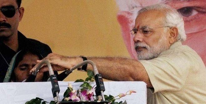 Narendra Modi adjusting the mike for village head
