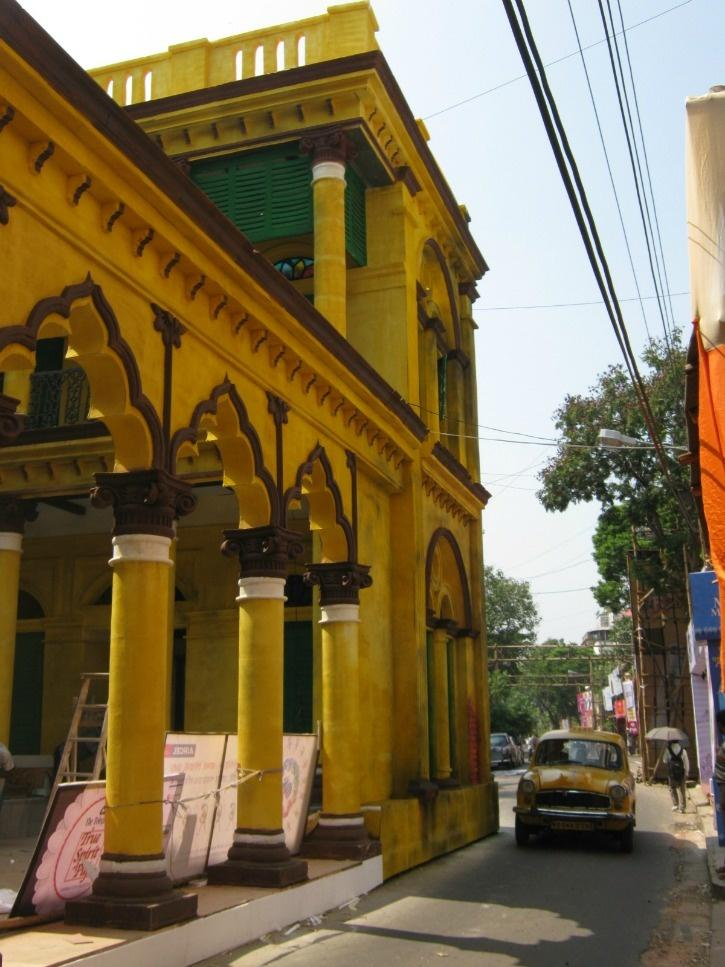 A pandal replicating an old colonial house, in the middle of a road