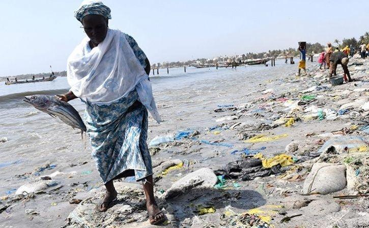 A woman holding a fish walks on tyre and plastic waste on June 1, 2019 in Dakar