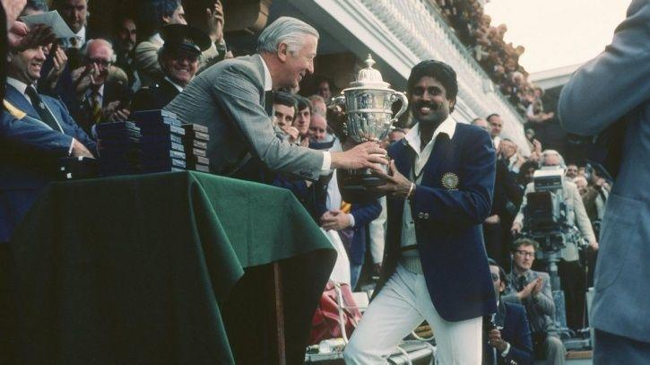 Kapil Dev holding the world cup trophy.
