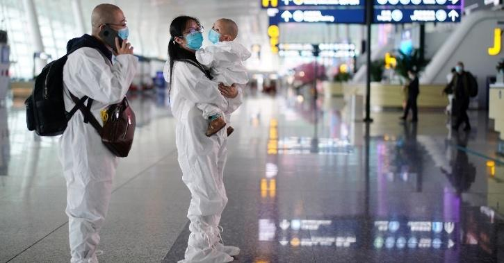 Travellers in protective suits are seen at Wuhan Tianhe International Airport.