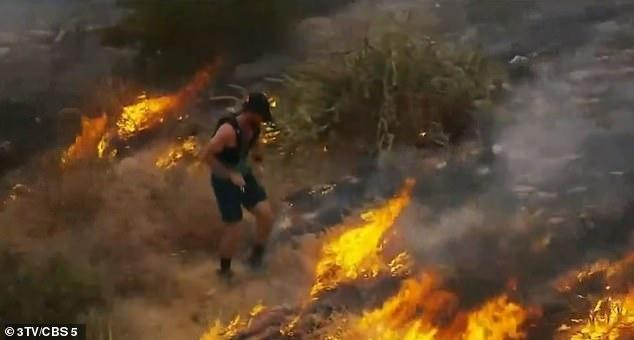 Jogger is spotted by TV helicopter trying to put wildfire