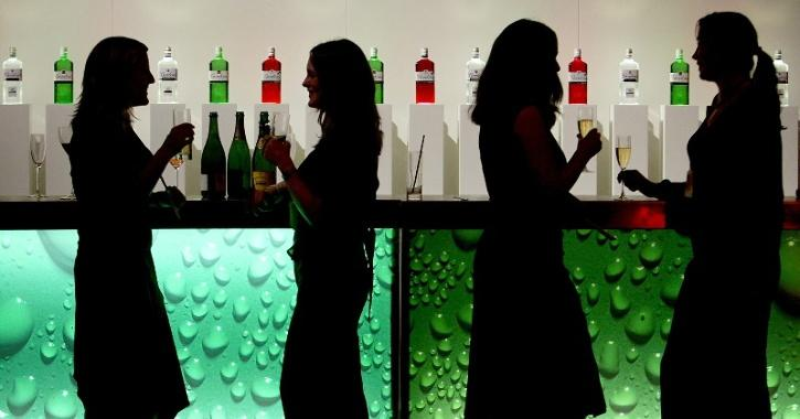 people standing near a bar counter with alcohol bottles in the background