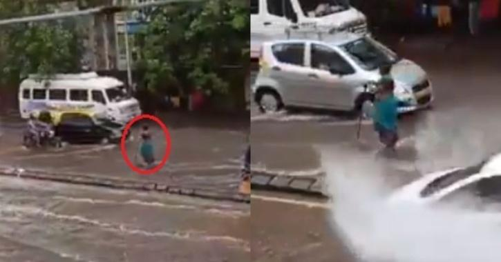 Woman stands on road to warn drivers of manhole