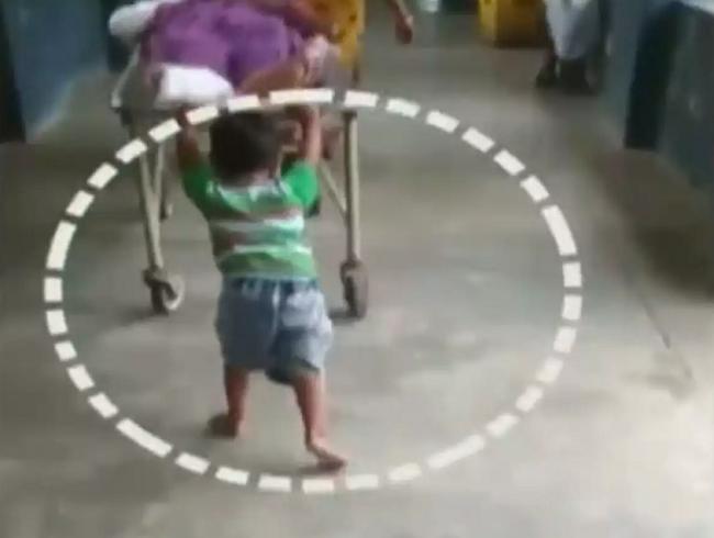 child pushing stretcher