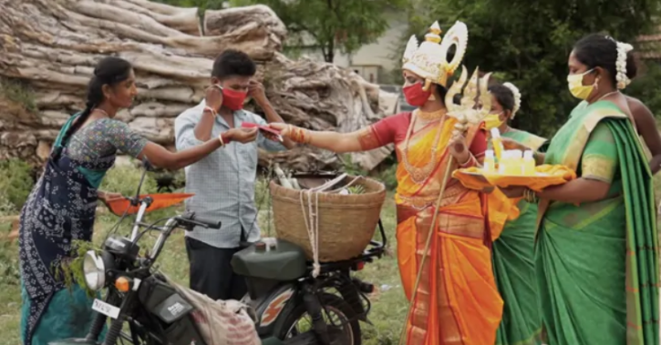 Woman dressed as goodess distribute masks