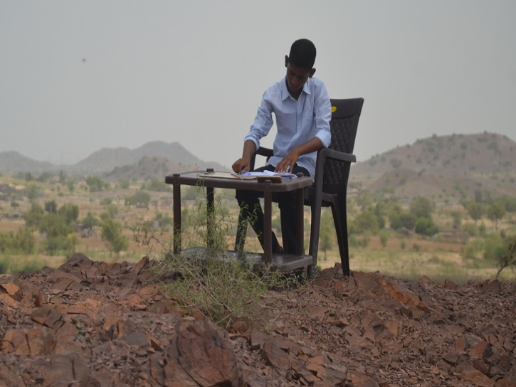 Boy studying on mountain top