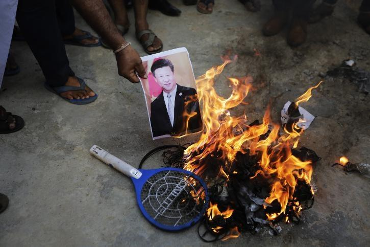 An Indian man burns a photograph of Chinese president Xi Jinping during a protest against China in Ahmedabad.