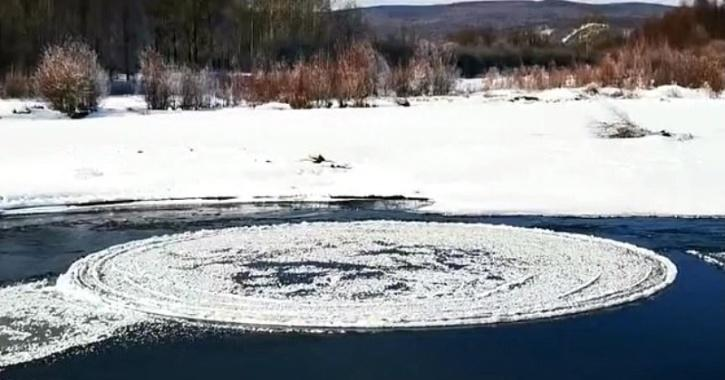 The ice disc can be seen rotating in an anti-clockwise direction along a partially frozen waterway.