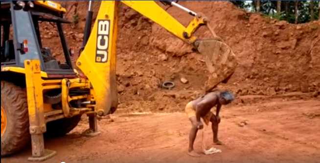 man gets his back scratched from JCB