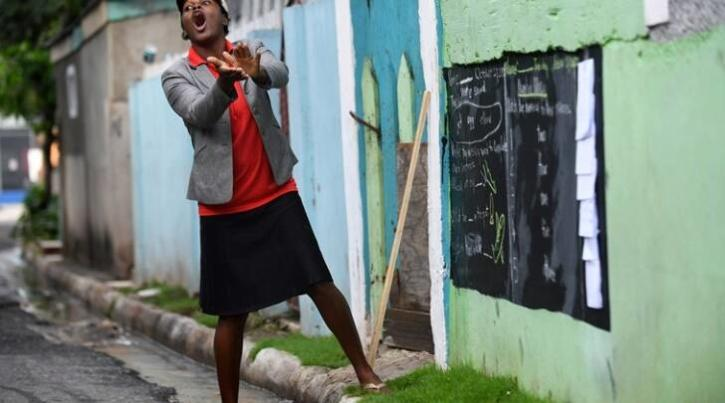 Educator Taneka Mckoy Phipps writes a lesson on a blackboard painted on a zinc fence in Jamaica.