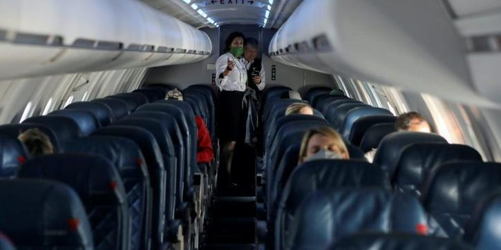 inside-of-a-plane-as-a-crew-member-assists-one-passenger-5f914b4561833