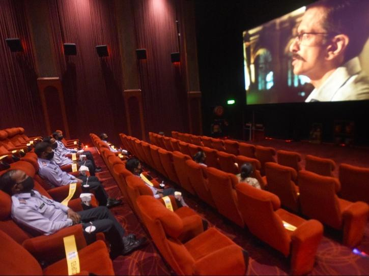 people watching movie in cinema hall after lockdown.