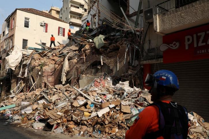 A rescue team searches through rubble of damaged buildings