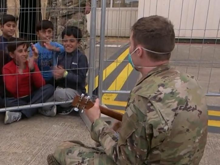 Soldier plays music for Afghan refugees