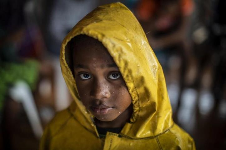 A girl protects herself from the heavy rains