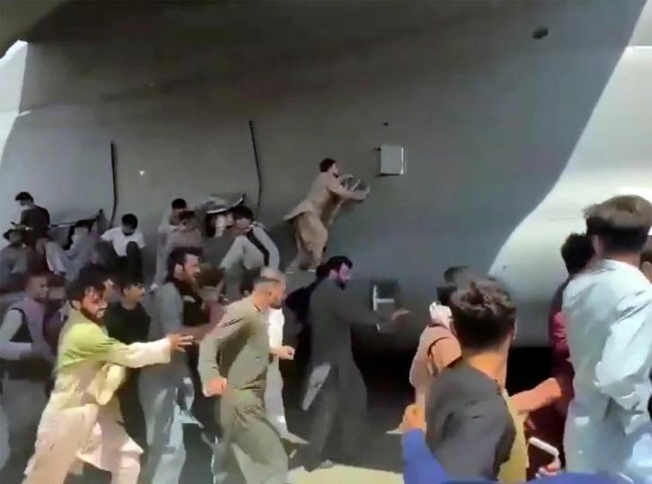 Afghans trying to cling onto Us military plane.