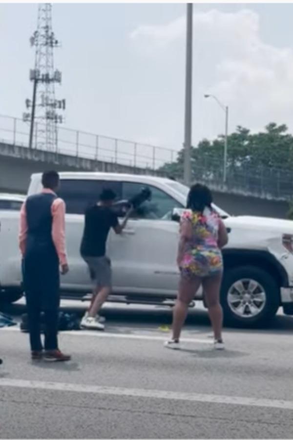 guy trying to break car window