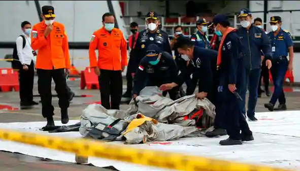 Indonesian rescue members carry what is believed to be the remains of the Sriwijaya Aeroplane flight SJ 182