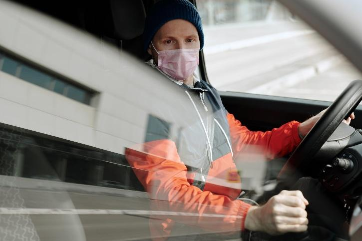 man in face mask driving cab