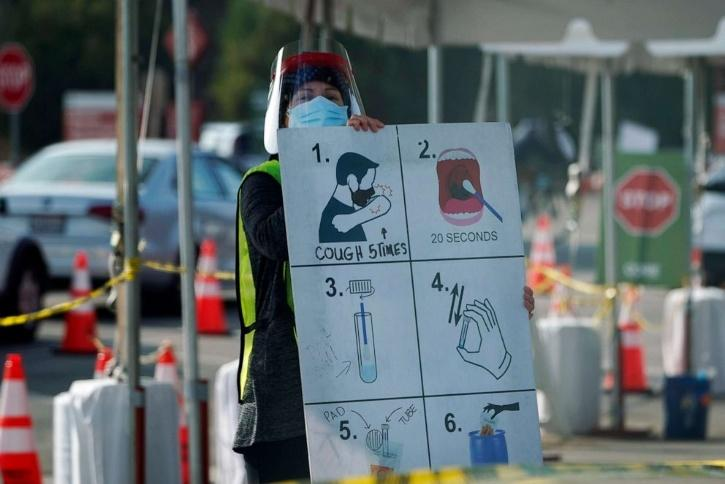 A worker gives instructions to motorists at a COVID-19 testing site on Jan. 5, 2021, in Los Angeles.