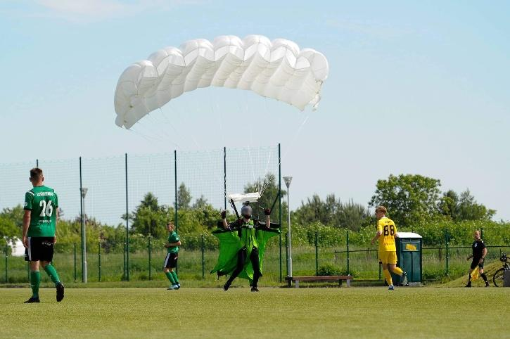 man parachutes into football game