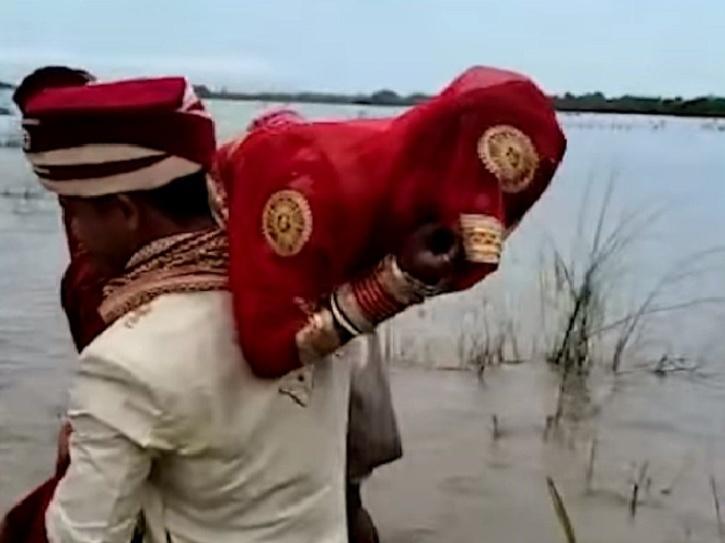 groom carries bride on shoulder across river after boat gets stuck on sand