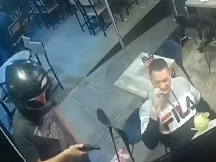 Man calmly eats chicken wings while being robbed at gunpoint