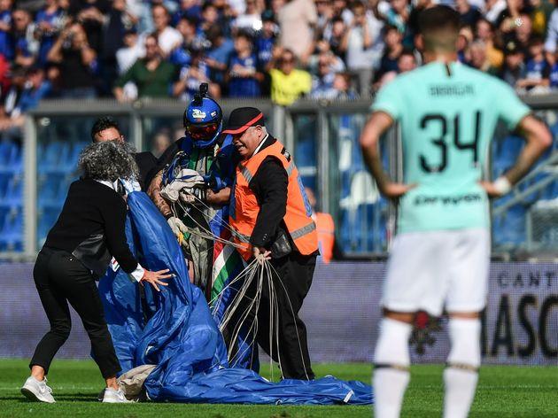 Man parachutes into football stadium