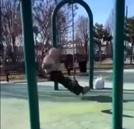 Elderly man performs stunt on swing set