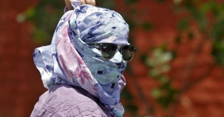 A woman walks along the road with her face covered to protect herself from sun stroke on a hot summer day