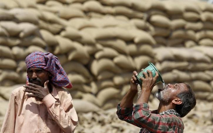 Labourers drinking water to quench their thirst as heat wave grips India