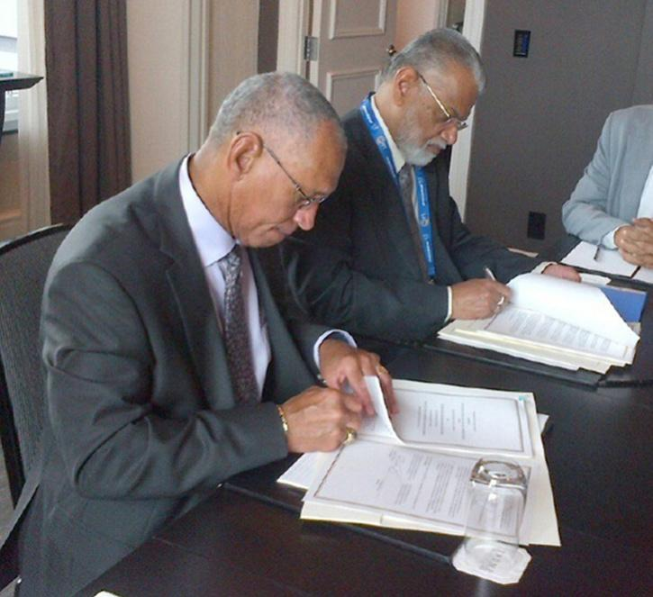 NASA Administrator Charles Bolden (left) and ISRO Chairman K. Radhakrishnan signing documents in Toronto on Sept. 30, 2014, to launch a joint Earth-observing satellite mission and establish a pathway for future joint missions to explore Mars.