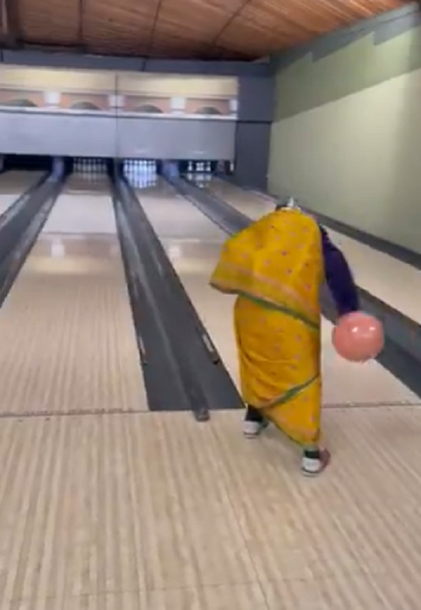 In the video, an elderly woman can be seen bowling in an alley.The grandmother manages to hit a strike, turns around and then ensures that her mask is properly covering her face.