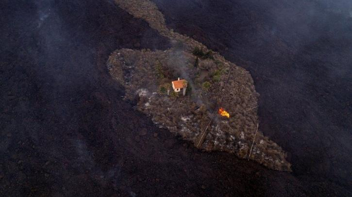 Lava flows surrounded a house following the eruption of a volcano in the Canary Islands