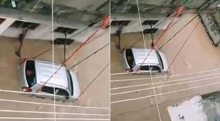 car tied with rope to keep it from being carried away in floodwater