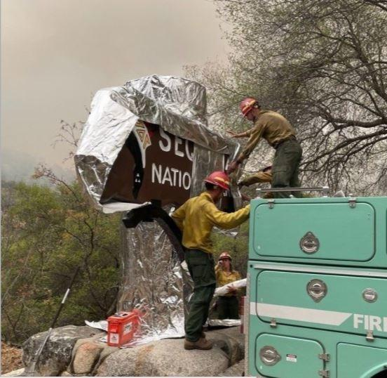 Firefighters cover a sign at Sequoia National Park, California, U.S., in this picture obtained by Reuters on September 17, 2021. Sequoia and Kings Canyon National Park Service/Handout via REUTERS