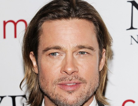 Brad Pitt trips while carrying daughter