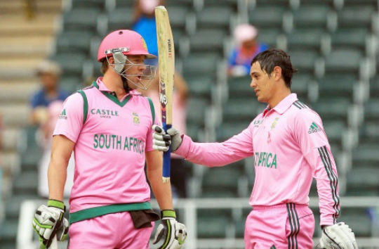Quinton de Kock, raises his bat after reaching a century as captain Abraham Benjamin de Villiers, left, watches during their 1st One Day International cricket match against India at Wanderers stadium in Johannesburg, South Africa. (Photo: AP)