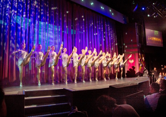 The Rockettes, best-known for dancing at the Radio City Christmas Spectacular, do their signature kick line during christening ceremonies