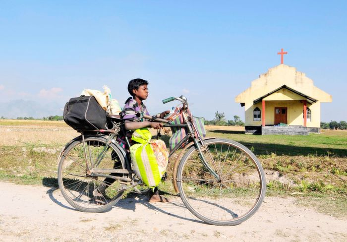 Tribal carrying his stuff on a bicycle