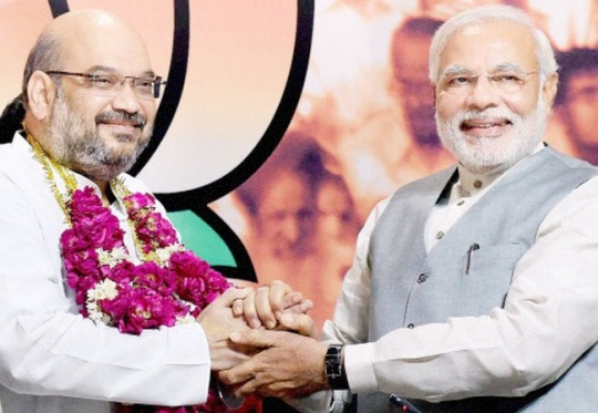 Prime Minister Narendra Modi greets the newly elected BJP President Amit Shah
