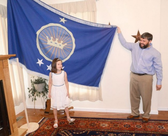 Jeremiah Heaton and his seven year-old daughter, Princess Emily, show the flag