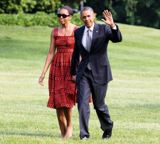 President Barack Obama waves as he walks with first lady Michelle Obama