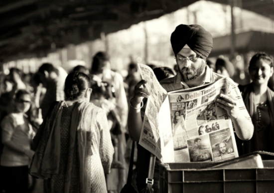 Indian reading paper at station
