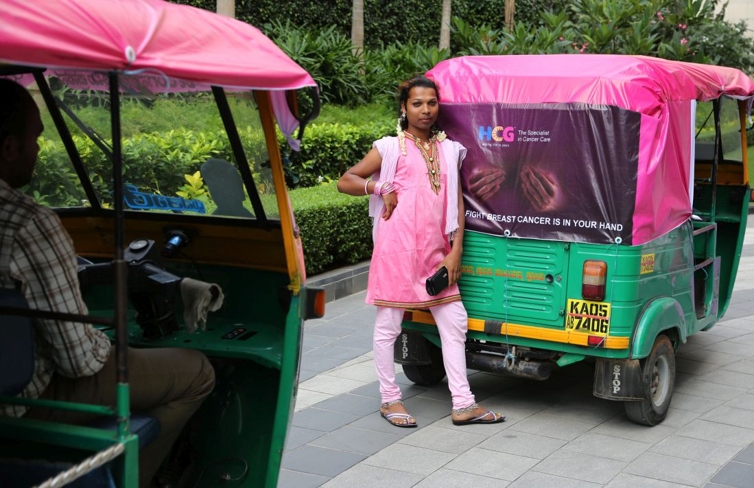 A member of India's transgender community stands next to a pink auto
