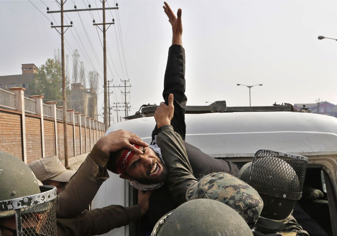 A Kashmiri Shiite Muslim shouts slogans as police detain him