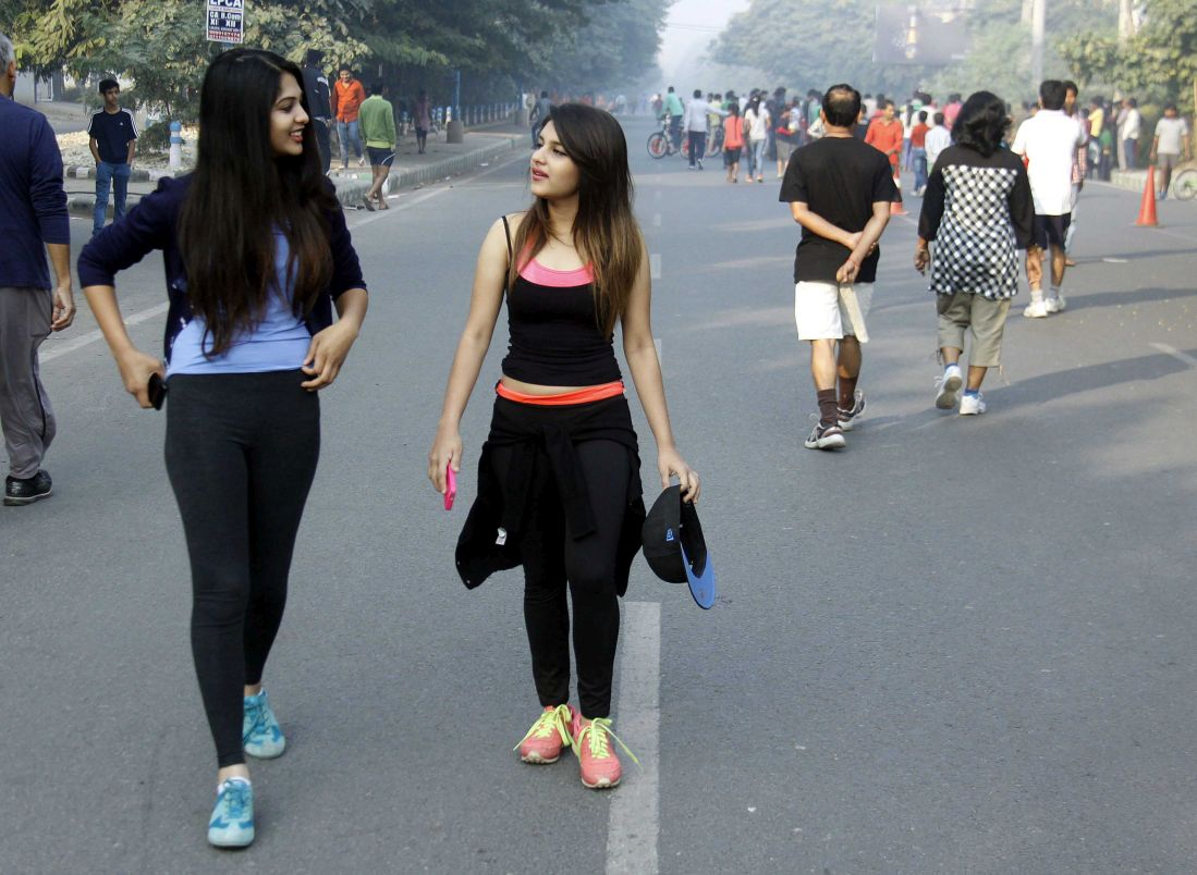 Two girls walking on the road after