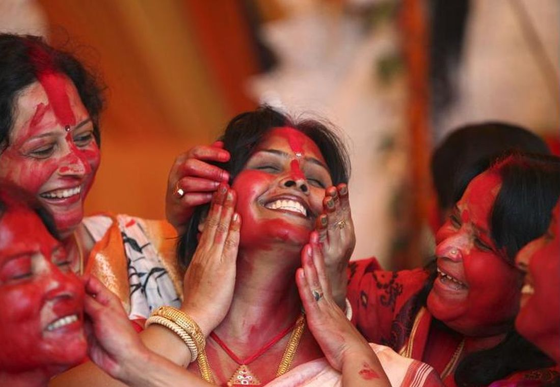 Women apply Sindur on the face of a woman during Durga Puja