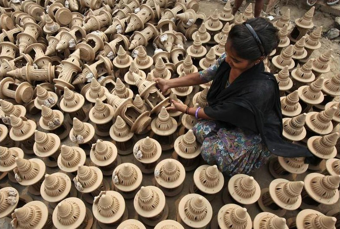 A girl puts earthen temple models to dry in the sun
